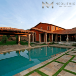 A calm and blue swimming pool with a Reclaimed pool column on the side