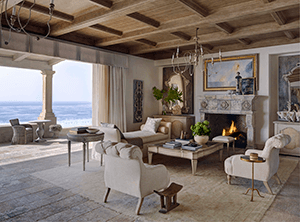 A living room with Reclaimed Stone Fireplace Mantels on it adding a beautiful ambiance to the place
